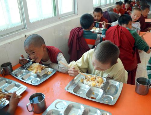 Bambini mentre mangiano nella mensa, costruita da ASIA nel 2009, della scuola di Derge.